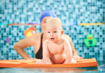 Horizontal picture of a cute little child spending fun time in swimming pool. A boy is crawling on a floating mat, mother is behind him supporting. Concept of active leisure