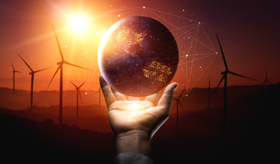 Concept of sustainability development by alternative energy. Man hand take care of planet earth with environmentally friendly wind turbine farm and green renewable energy in background.