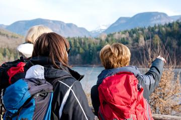 3 donne di mezza età osservano il panorama montano di un lago in Italia