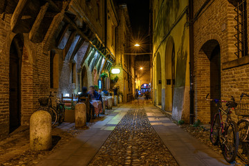 Wall Mural - Cozy street with old houses in Ferrara, Emilia-Romagna, Italy. Ferrara is capital of the Province of Ferrara.