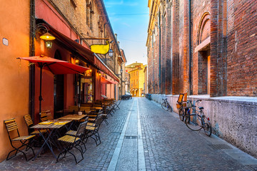 Wall Mural - Cozy street with old houses and tables of restaurant in Ferrara, Emilia-Romagna, Italy. Ferrara is capital of the Province of Ferrara.