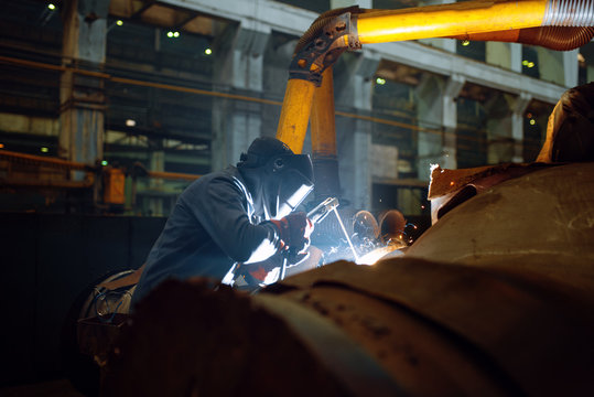 Welder in mask works with metal pipe on factory