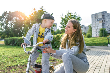 Happy woman mom, rejoices has fun with little boy child 4-5 years old, summer city. Rest on weekend. Emotions of fun joy and happiness. Help care balance support cycling, fitness sports training.