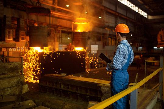 Master steelmaker at furnace, steel factory