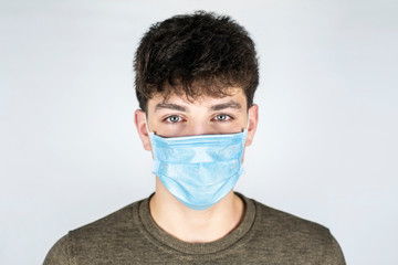A teenage boy in a medical mask on a light background, his eyes are red and tearful because he has a cold in college.  Medical prevention concept