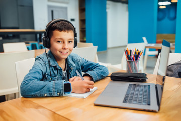 Child concentrated boy with laptop doing homework with headphone.