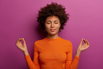 Obraz Peaceful determined curly young Afro American woman makes zen gesture, has yoga breathing practice, meditates indoor, closes eyes and wears orange jumper, isolated over vibrant purple background - fototapety do salonu