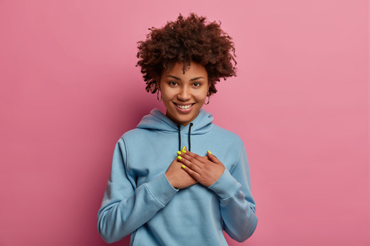 Pretty smiling Afro American woman makes grateful gesture, appreciates heartwarming words, wears casual blue hoodie, expresses positive emotions, isolated over pink background. Thankful girl indoor