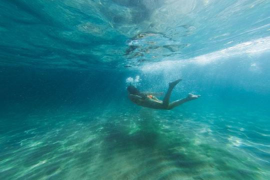 A girl in a bikini diving underwater