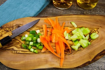 Close up of isolated sliced fresh spring onions (scallions), carrots, cucumbers on wooden olive tree cutting board and japanese kitchen knife. Blue napkin, oil bottles and wood table background.