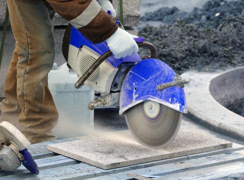 Worker cutting stone block by cutter machine