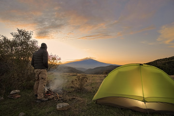 Fotorollo Camping Man Looking Etna Mount By His Illuminated Tent At Sunrise, Sicily