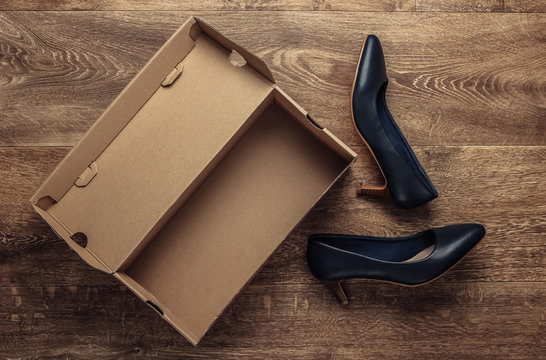 New leather heeled shoes with a cardboard box on the floor. Top view