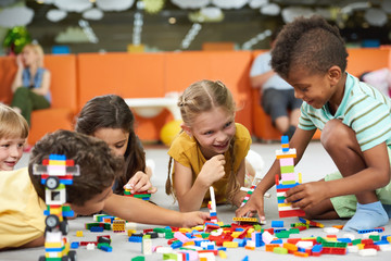 31.07.2017 - Kyiv, Ukraine. Group of funny kids playing with block toys indoor. Cute kids playing together indoor. Preschool early education.