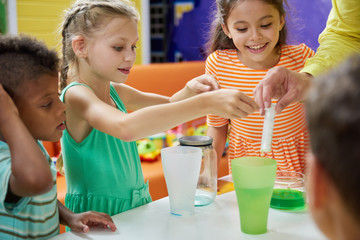 Kids doing chemical experiment at entertainment center. Flasks with colorful liquid on table. Childrens party entertainment.