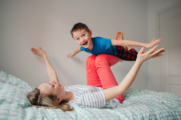 Caucasian mother and boy son playing in bedroom at home. Mom rocking child on her knees feet legs. Family having fun together. Happy candid authentic childhood lifestyle.