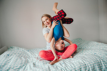 Smiling Caucasian mother and boy son playing together in bedroom at home. Mom holding her child upside down and laughing. Family having fun. Happy childhood candid authentic lifestyle.