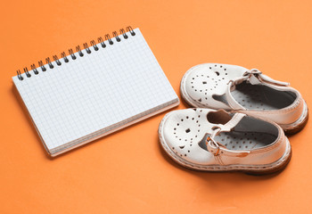 Children's leather sandals on orange background with notebook for copy space Wall mural
