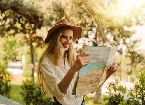 Blonde woman in a felt hat looks at city map and walks through an unfamiliar city outdoor