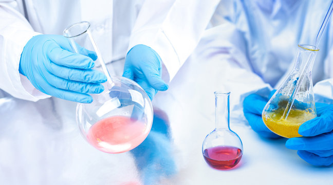 The hands of the chemists in gloves holding the flasks. Experiments with chemical liquids. Demonstration of experiments in chemistry lessons. Testing of raw materials for the chemical industry.