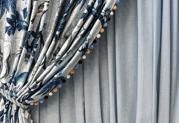 Curtain with a blue floral pattern and multi-colored pompons on the edge.