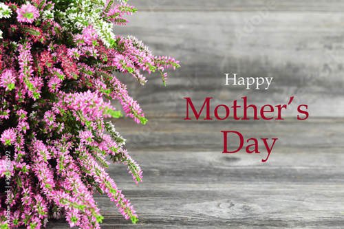 Happy Mothers Day card. Heather flowers on wooden background