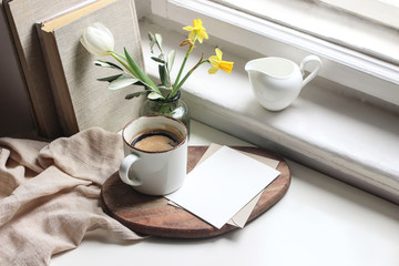 Cozy Easter spring still life. Greeting card mockup scene. Cup of coffee, books, wooden cutting board, milk pitcher and vase of flowers on windowsill. Floral composition. Yellow daffodils and tulip.