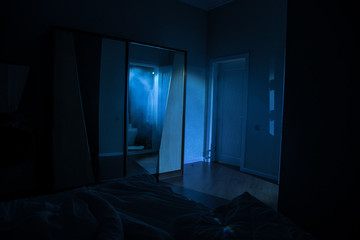A creepy bedroom scenery, Silhouette of scary person standing reflected in mirror with mist and toned light.