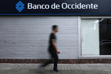 A man walks in front of a Banco de Occidente branch in Bogota