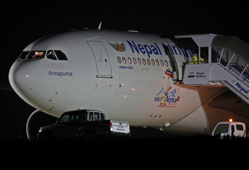 An official in protective suite prepares to evacuate 175 Nepalese nationals from a Nepal Airlines Airbus A330-200 plane arriving from coronavirus-stricken Chinese city of Wuhan before they were sent to be quarantine at Tribhuvan International Airport in Ka