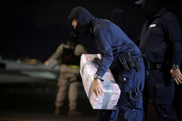 A police officer carries a package containing cocaine seized during an operation in the Caribbean, at the air base of the Ministry of Security in Alajuela