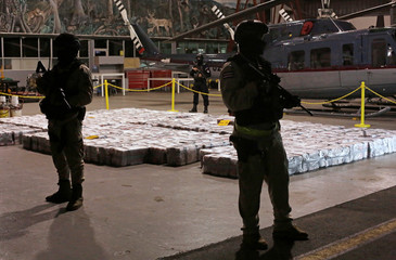 Police officers are seen in front of packages containing cocaine seized during an operation in the Caribbean, at the air base of the Ministry of Security in Alajuela