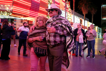 People listen to entertainment music along the Fremont Street Experience, a five-block entertainment district, in historic downtown Las Vegas, Nevada