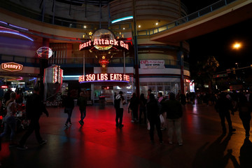 People walk along the Fremont Street Experience, a five-block entertainment district, in historic downtown Las Vegas, Nevada