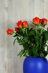 a bunch of red roses in blue vase