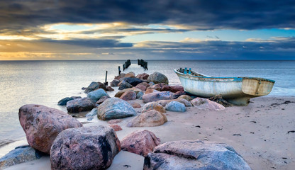 Abandoned fishing boat after storm near a village of fishermen, Baltic Sea