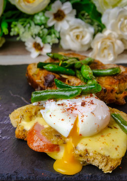 Breakfast on a black slate blackboard. Croutons with cheese, sausage, poached egg, green green beans.