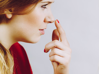 Girl touching her nose, side view