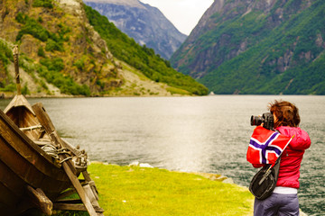 Tourist with camera near old viking boat, Norway