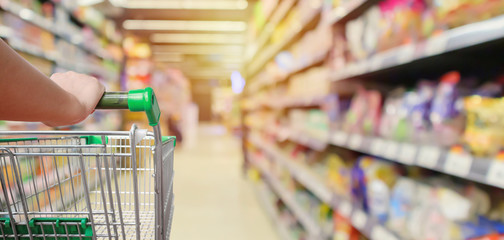 shopping cart in supermarket aisle with product shelves interior defocused blur background