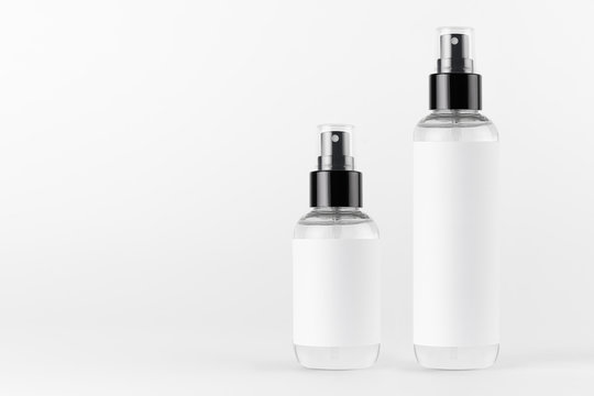 Tall, low transparent spray dispenser bottle for cosmetics with white label on white background, mock up for branding,  presentation, design.