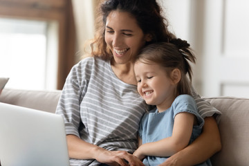 Happy young mother watching funny cartoons on computer with daughter.