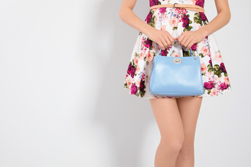 Young woman wearing floral print dress with stylish handbag on light background, closeup. Space for text Wall mural