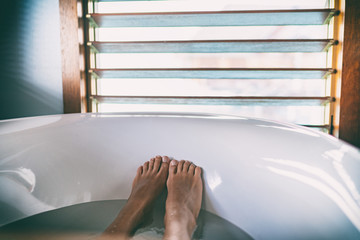 Bath soaking feet woman relaxing in hot bathtub water relaxation wellness foot therapy.