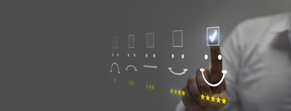 Businessman pressing smiley face emoticon on virtual touch screen. Customer service evaluation concep