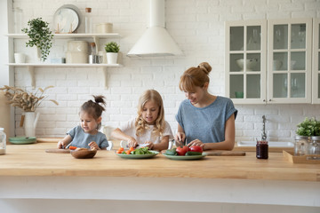 Caring mom cooking together with little daughters Fototapete