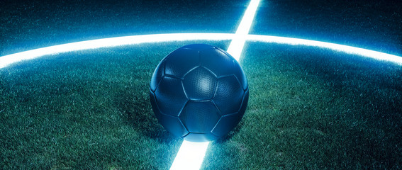 Soccer ball on glowing lines on a field at night