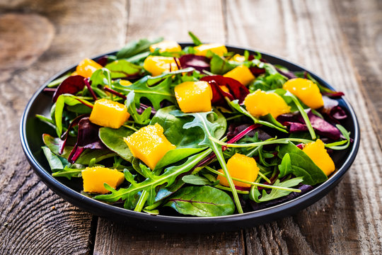 Vegetable salad with mango on wooden background