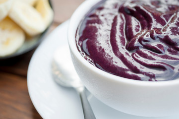 Fresh bowl of purple Amazonian acai in a clean white bowl with a side of banana slices on wooden table in Brazil