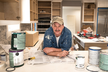 Male painter splattered with paint and holding a wet paint brush in messy home kitchen during residential home remodel with empty paint cans stacked around him, cabinet doors off and open